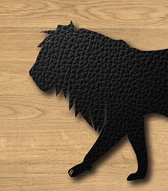 A black leather lion silhouette on a grainy wood background.