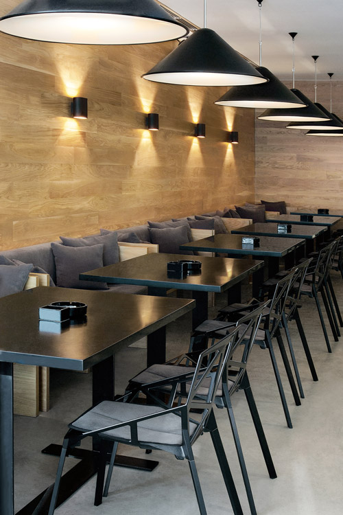 A modern restaurant interior design with wooden wall cladding, Tom Dixon lights and Konstantin Grcic chairs.