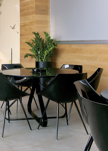 A restaurant dining area with Driade chairs by Philippe Starck and custom-made tables by Reform.