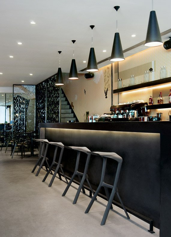 A stylish black bar counter with Magis bar stools and Tom Dixon pendant lights.