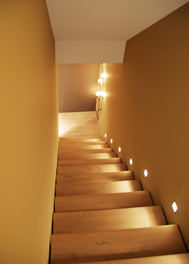 A commercial staircase with a minimalist design using distressed oak floorboards and recessed wall lights.
