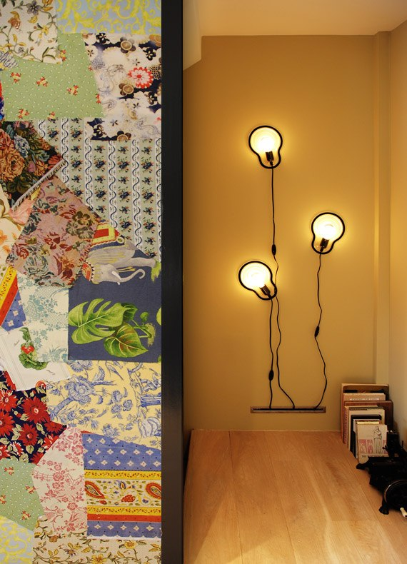 A fabric patchwork wall in front of an ochre wall with designer bulb lights crawling up.
