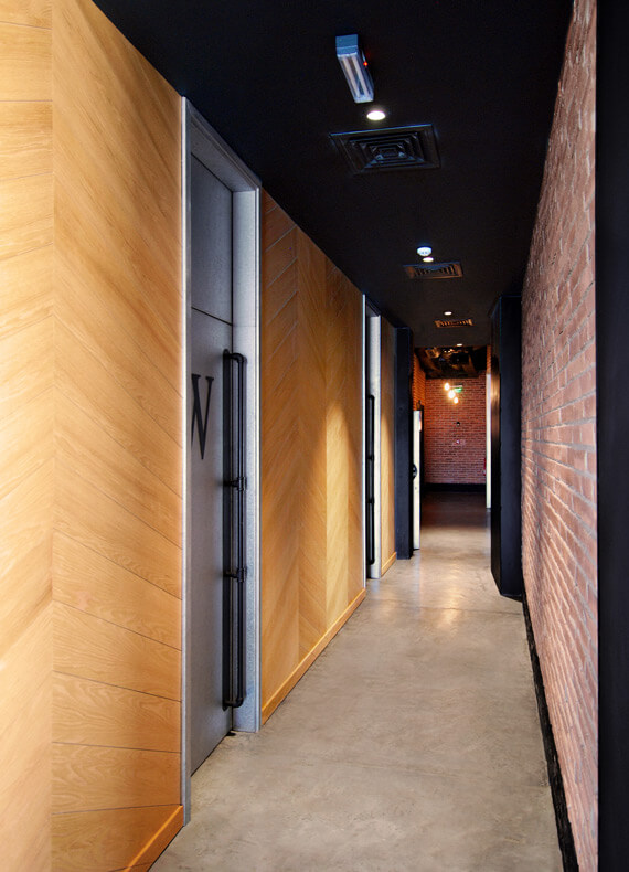 A corridor with a red brick wall on the right side and a wooden herringbone wall on the left.
