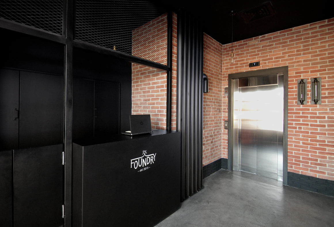 The entrance¬¬ to The Foundry restaurant with red bricks walls and a black metal reception.