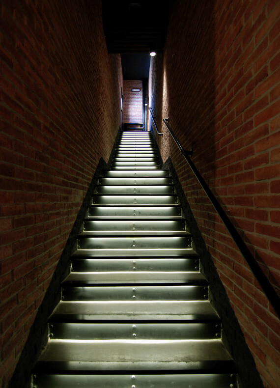 The stairway of an industrial restaurant bar which combines a sleek modern design with timeworn charm.