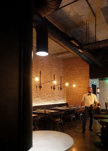 The interior of an industrial style restaurant with ambient lighting creating a warm dramatic glow against red brick walls.
