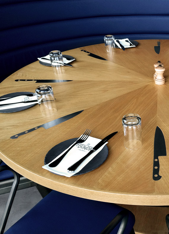 A round oak dining table personalized with metal knife inlays.