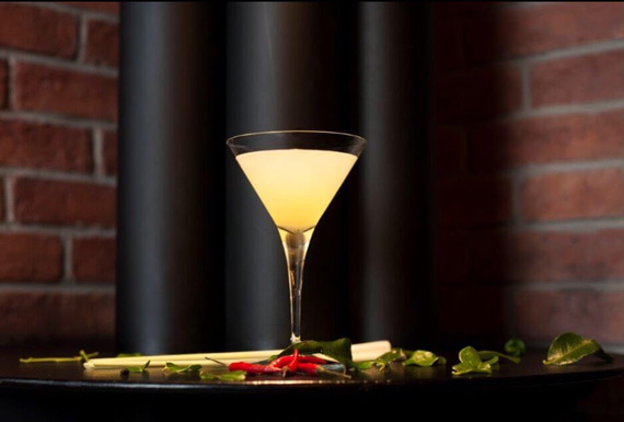 A martini cocktail in front of black pipes and red bricks.