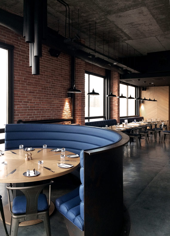A warehouse chic restaurant decor with tailormade blue leather booth seating, oak tables and black steel pipe luminaires.