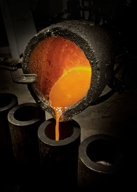 Molten metal being poured from a ladle into casting molds.