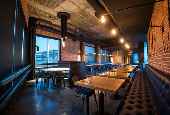 The atmospheric open-plan dining area of an industrial restaurant featuring exposed structural elements.