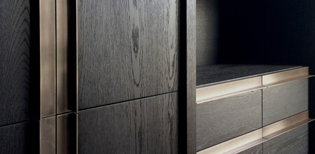 A bespoke black oak cabinet with elegant brushed bronze pull handles.