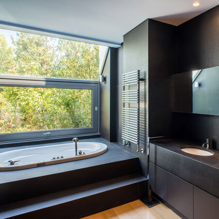 A modern bathroom design in black slate featuring a step-up bathtub with a nature view.