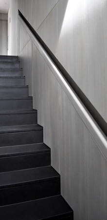A black natural stone staircase with a light grey oak wall and a flush handrail in recess.
