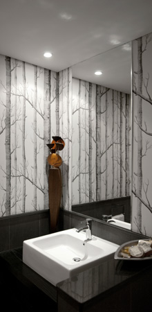 A black and white bathroom design with stone tiles, tree illustration wallpaper and a flush mirror.