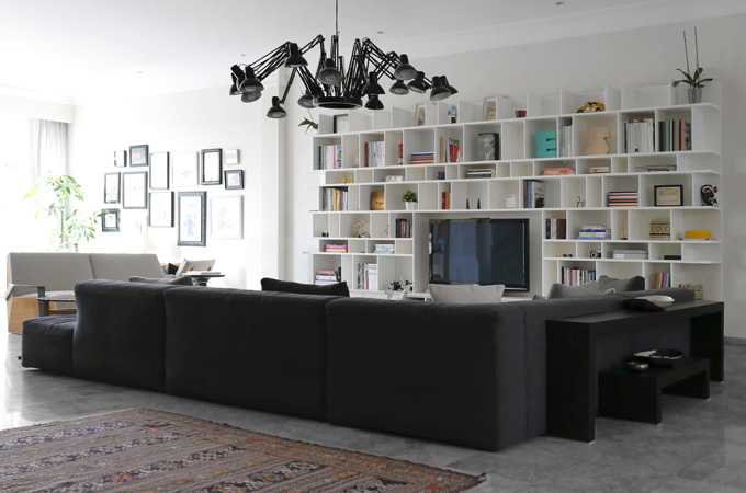 A contemporary living room with a large white bookcase, a dark sectional sofa and an industrial style chandelier.