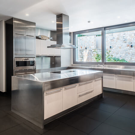 A contemporary stainless-steel kitchen with white cabinets and a black slate floor.