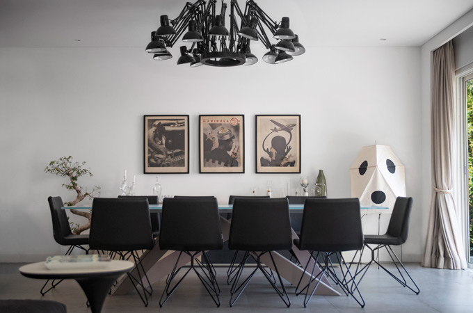 An eclectic minimalist dining room featuring a spider chandelier, black leather chairs, a glass table and a Noguchi lamp.
