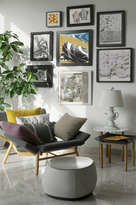 Eclectic interior design ideas - a feature wall with picture frames, a teapot lamp and a stylish armchair with footstool.