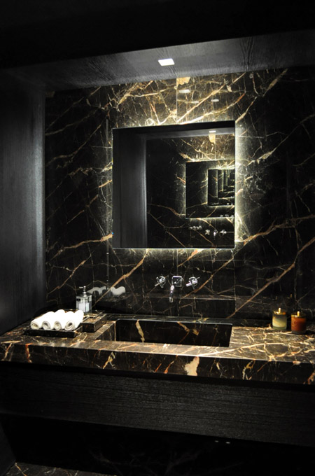 A dramatic bathroom design using Port saint Laurent marble and opposing mirrors creating multiple receding reflections.