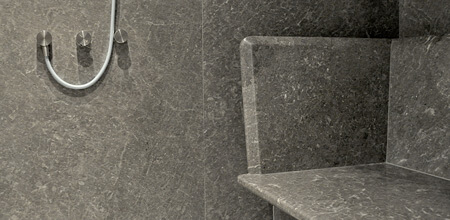 A walk-in shower in grey marble with a built-in marble bench.