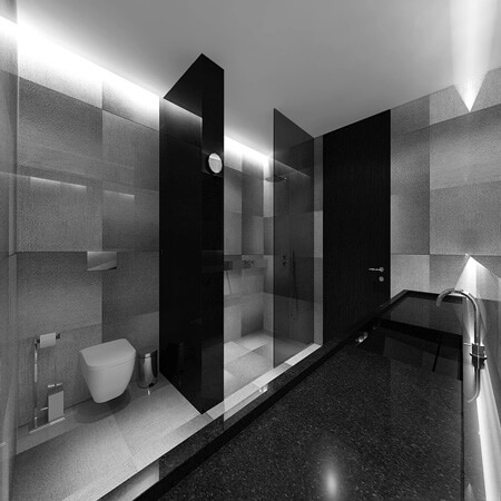A sleek monochrome bathroom design with grey gradient tiling, black glass partitions and a long black marble sink.
