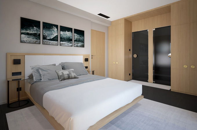 A stylish bedroom with a floating bed, wood finish wardrobes and black glass doors to the ensuite bathroom.