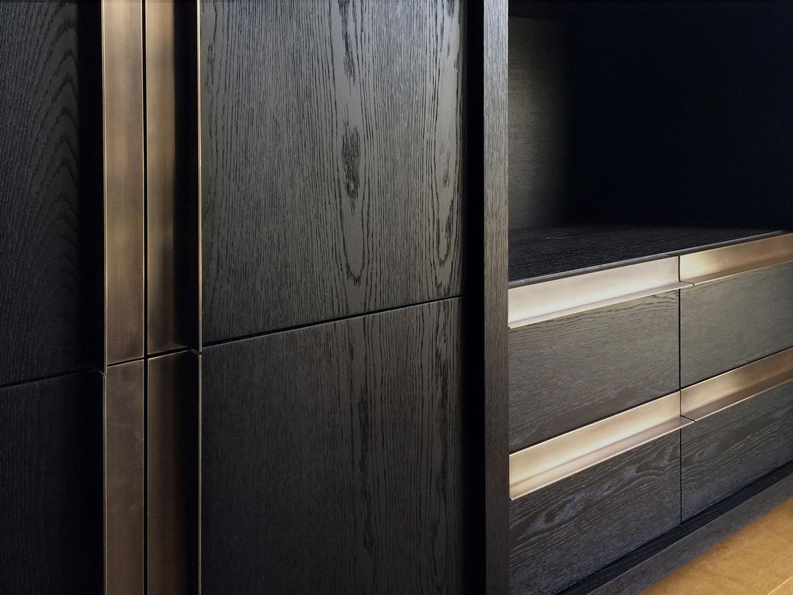 A custom-made modern sideboard in a dark wood finish with sleek brass pull handles.