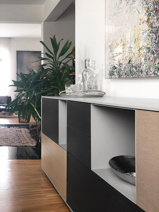 An eclectic dining area with a contemporary minimalist sideboard and an art installation made of shredded paper.