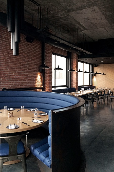 An industrial chic restaurant interior with blue leather seating, brick walls and exposed structural elements.