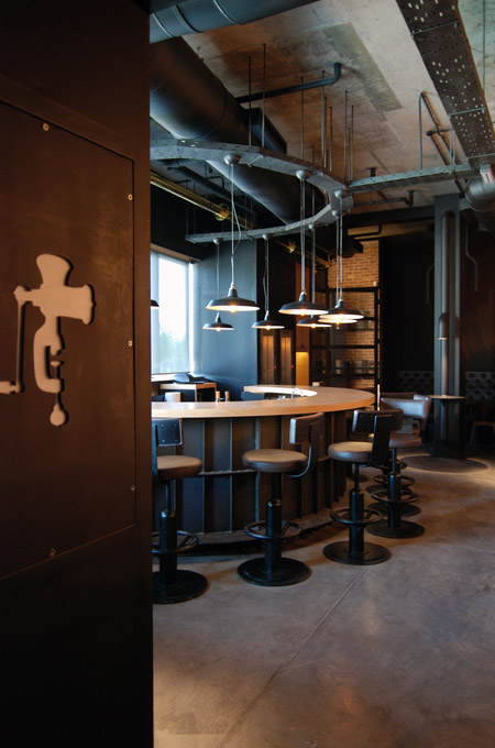 An industrial style bar interior with concrete floors and exposed architectural elements.