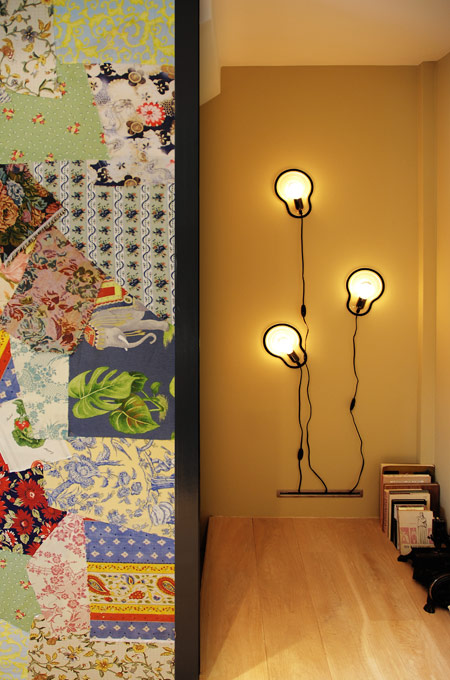 A feature patchwork fabric wall and an ochre wall with a light installation.
