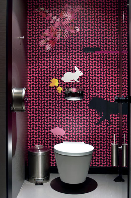 A playful commercial restroom featuring pink and black patterned wallpaper with wildlife silhouettes.