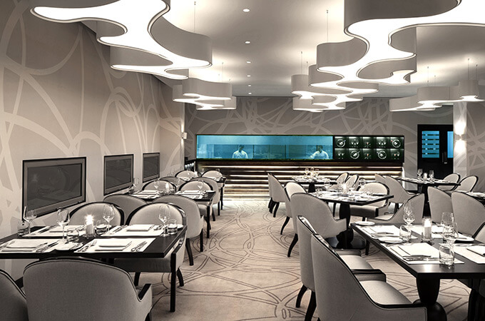 A modern luxury hotel restaurant featuring a custom designed carpet with matching wallpaper and amoeba pendant lights.