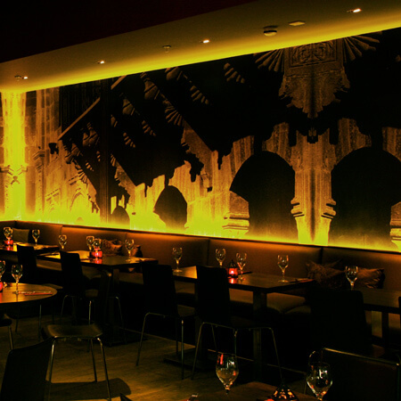 A restaurant interior with a custom designed wall mural and atmospheric lighting.