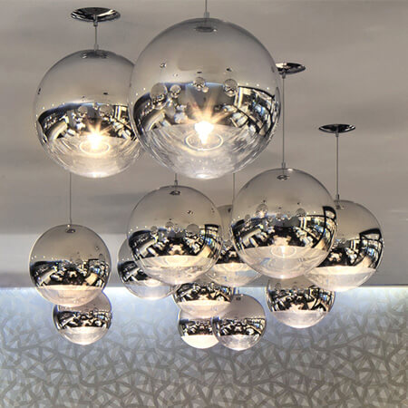 A feature ceiling design with an installation of asymmetrically hanging Tom Dixon mirror ball lights.