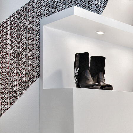 A retail display stand in white lacquer with recessed lighting, in front of brown and white patterned wallpaper.