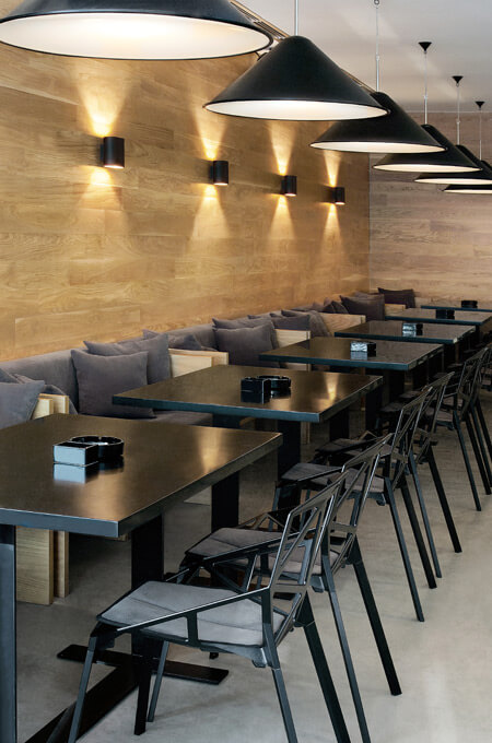 An urban dining environment with wooden walls, large pendant lights, black seating and concrete floors.