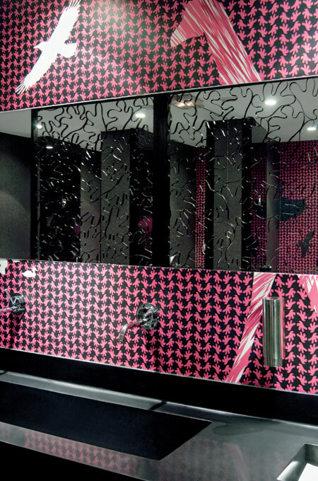 A restaurant bathroom vanity with a long black corian sink, thin horizontal mirror and fuchsia wallpaper.