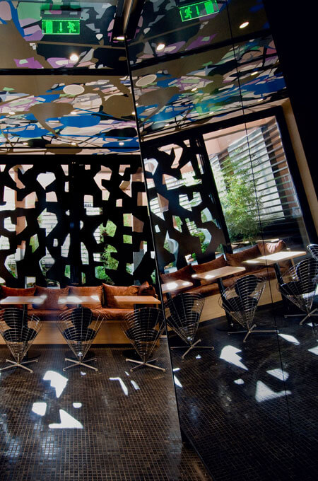 A contemporary wine bar with a psychedelic ceiling and window screens.