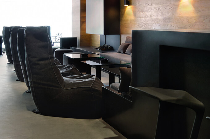 A contemporary minimalist bar lounge in a dark color scheme.