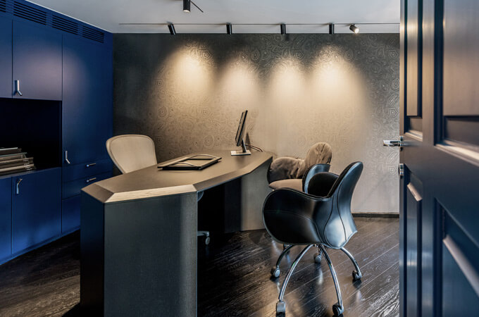 A custom-made polymorphic desk in an atmospheric executive office with a moody color scheme.