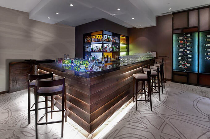 A hotel bar design using distressed wooden planks with hidden lighting, black marble counter and backlit shelving display.