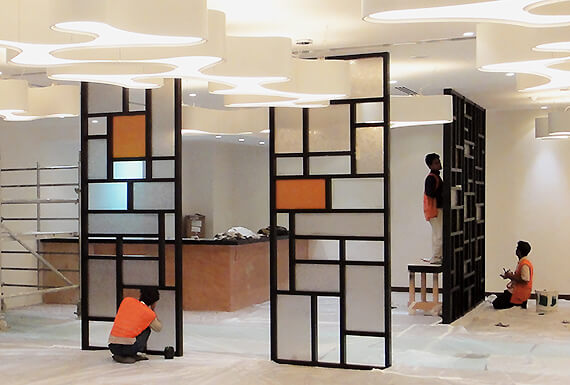 The construction of bespoke geometric partition screens using a wooden grid and frosted acrylic panels.