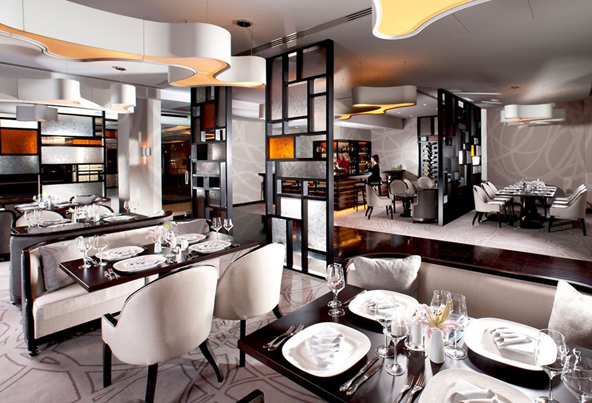 A restaurant design featuring a juxtaposition of geometric and organic forms in a neutral 2-tone scheme with orange accents.