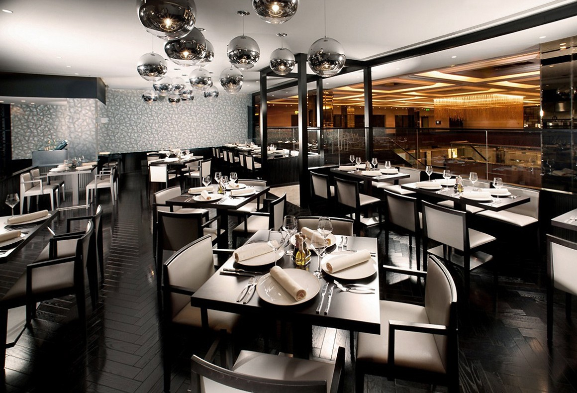 Interior design of an InterContinental Hotel restaurant with herringbone floors, patterned wallpaper and ball pendant lights.