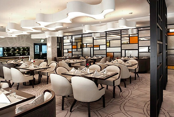 A modern hotel restaurant interior with classic references, rich cream and wood tones, and amoeba shaped pendant lights.