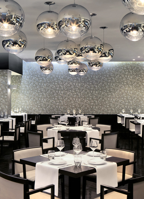 A classy casual style restaurant with clean lines, blue-tint wallpaper and Tom Dixon mirror ball pendant lights.
