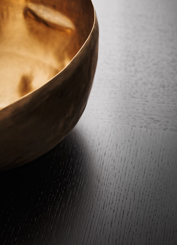 A gold decorative bowl on a dark wenge table surface.