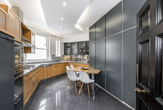 A modern kitchen with light oak and grey cabinets, granite countertop, marble floors and dining table.